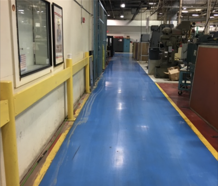 Commercial warehouse facility with dry blue flooring after water was removed..