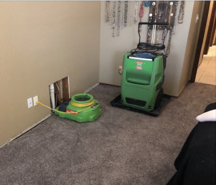 Air mover and dehumidifier drying affected area.