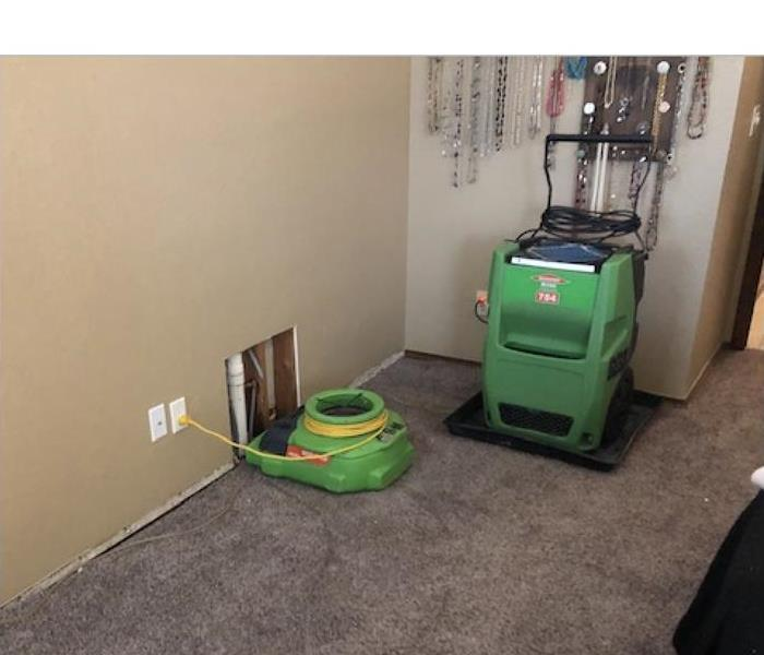 Air mover and dehumidifier drying carpet