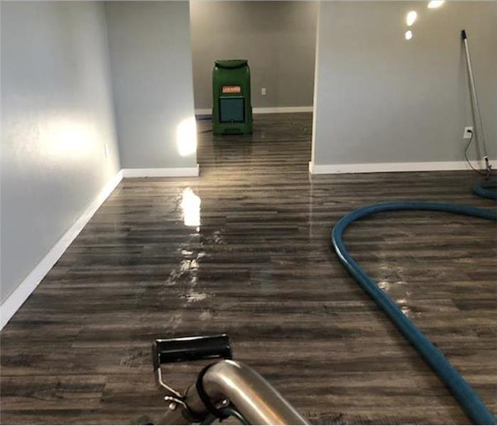 A dehumidifier and a water extraction vacuum placed on wooden floor