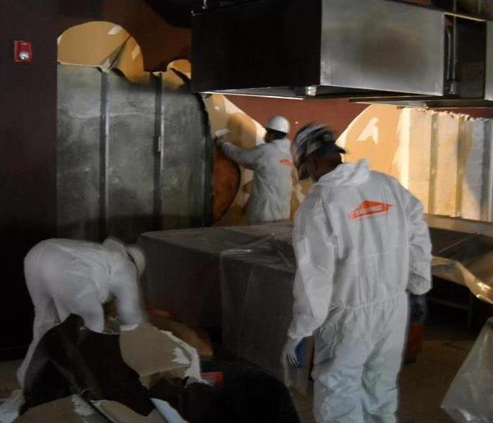Technicians wearing protective gear while cleaning a house from mold damage