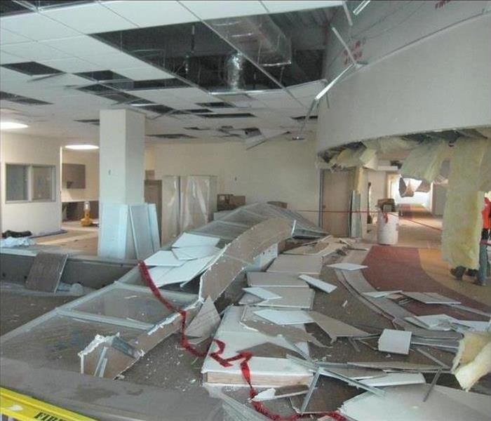 Ceiling collapsed after storm in a commercial building, pieces of ceiling tiles all over the floor. Concept storm damage